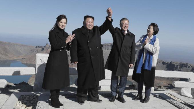 Korean leaders join hands on peak of North Korean volcano